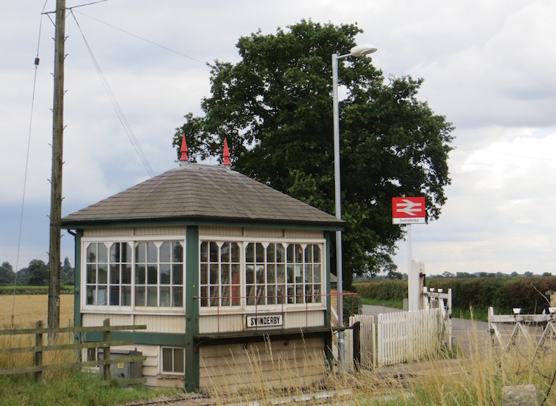 Swinderby Signal Box viewed from the front three-quarters, looking across the railway with the level crossing gates to the right