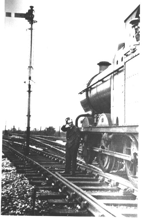 A puzzled railwayman looks at a signal in the middle of the track